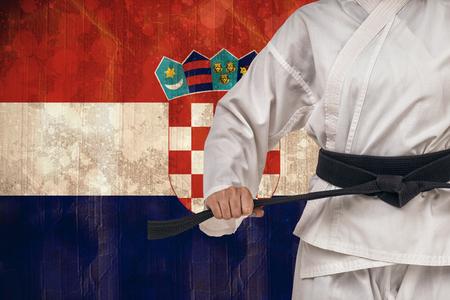 bandera croacia: Combatiente aprieta el cinturón de karate contra la bandera de Croacia, en efecto grunge Foto de archivo