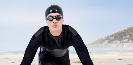 wetsuit: Confident swimmer in wetsuit against beautiful beach and blue sky