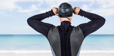 waters: Rear view of swimmer in wetsuit wearing swimming goggles against waters edge at the beach