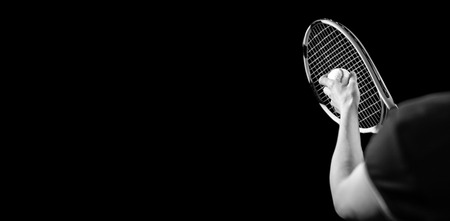 serve: Tennis player holding a racquet ready to serve on black background