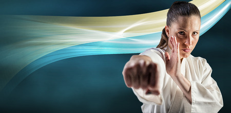 female fighter: Female fighter performing karate stance against black background
