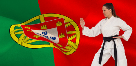 female fighter: Female fighter performing karate stance against digitally generated portugal national flag
