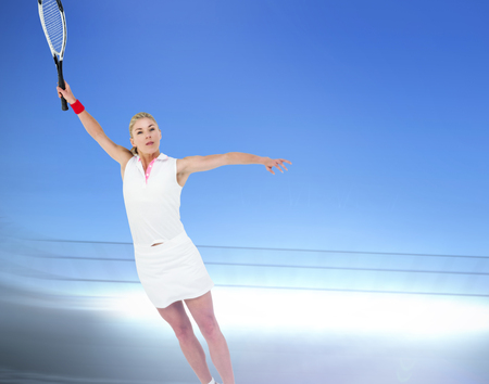 racket stadium: Athlete playing tennis with a racket  against large football stadium under bright blue sky