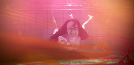 leisure centre: Pretty brunette smiling and offering her hand underwater in the swimming pool at the leisure centre