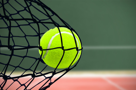 digitally generated image: Tennis ball with a syringe against digitally generated image of playing field Stock Photo