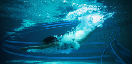 lane marker: Athletic swimmer smiling at camera underwater against feet of woman standing on the edge of the pool