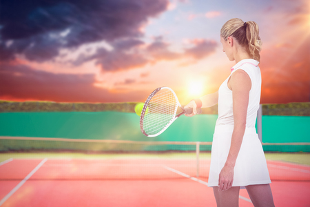 digitally generated image: Athlete playing tennis with a racket  against digitally generated image of tennis court