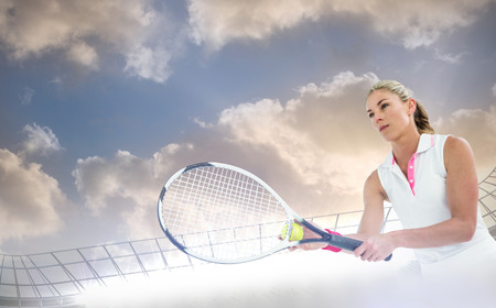 racket stadium: Athlete playing tennis with a racket  against large football stadium under cloudy blue sky