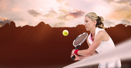 composite image: Athlete playing tennis with a racket  against composite image of landscape Stock Photo