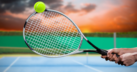 digitally generated image: Tennis player playing tennis with a racket  against digitally generated image of tennis court Stock Photo