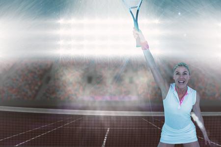 digitally generated image: Athlete celebrating after victory against digitally generated image of supporters in tribune