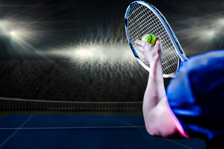 digitally generated image: Tennis player holding a racquet ready to serve  against digitally generated image of blue tennis court  illuminate by spotlight