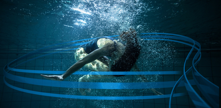somersault: Athletic swimmer doing a somersault underwater against feet of woman standing on the edge of the pool Stock Photo
