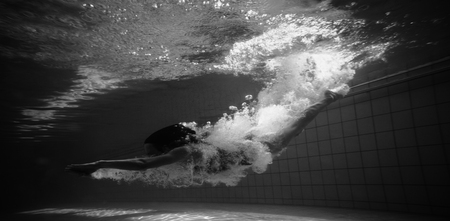 leisure centre: Athletic swimmer smiling at camera underwater in the swimming pool at the leisure centre