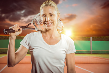 digitally generated image: Portrait of female tennis player posing with racket against digitally generated image of tennis court