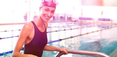 getting out: Fit swimmer smiling at camera getting out of the swimming pool at the leisure center Stock Photo