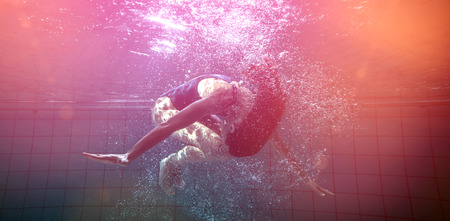 somersault: Athletic swimmer doing a somersault underwater in the swimming pool at the leisure centre Stock Photo