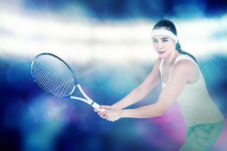 digitally generated image: Female athlete playing tennis against digitally generated image of spotlight against black background