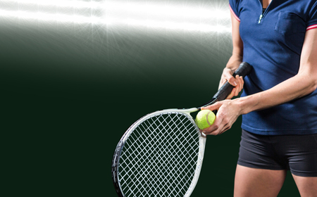 serve: Tennis player holding a racquet ready to serve  against spotlight Stock Photo