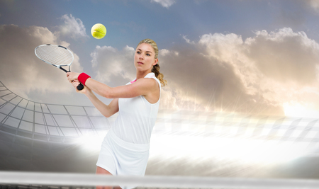racket stadium: Athlete playing tennis with a racket  against large football stadium under cloudy sky