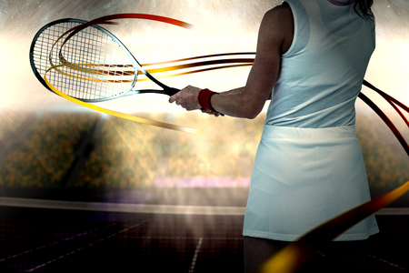 digitally generated image: Athlete playing tennis with a racket  against digitally generated image of supporters in tribune