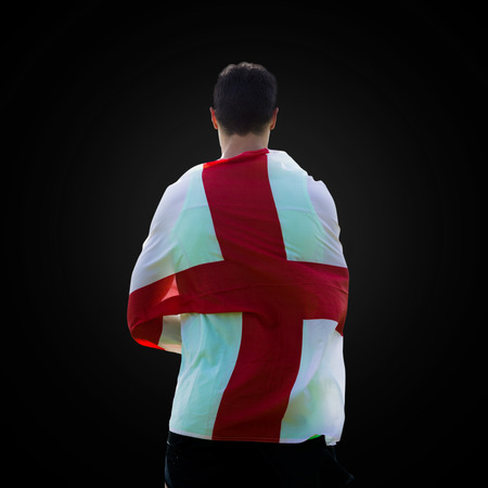 drapeau angleterre: Rear view of sportsman holding an England flag in a black background