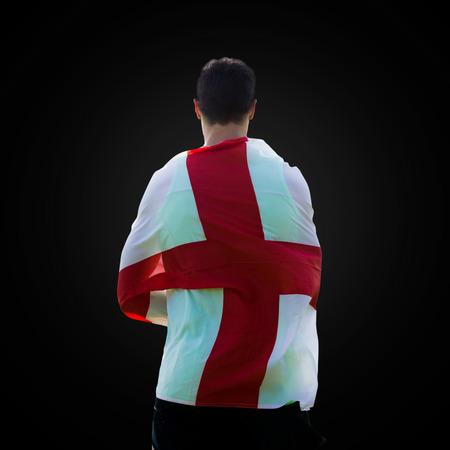 bandiera inghilterra: Vista posteriore di sportivo tiene una bandiera Inghilterra in uno sfondo nero