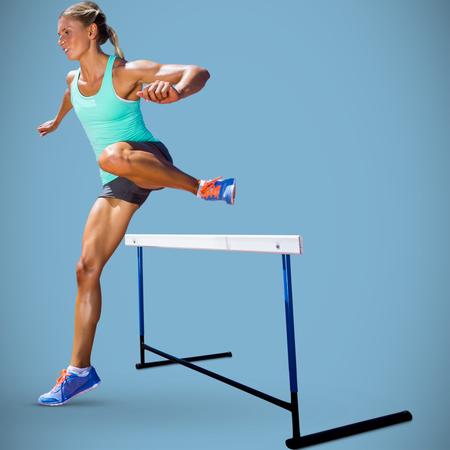 hurdles: Sportswoman practising the hurdles against blue background