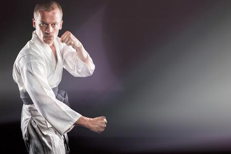 Fighter performing karate stance against black background