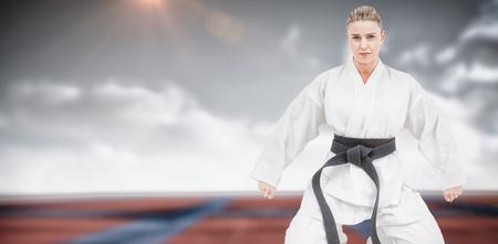 digitally generated image: Female athlete practicing judo against digitally generated image of bi colored sports ground Stock Photo