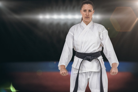 playing field: Female karate player posing on white background against composite image of playing field indoor