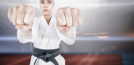playing field: Female athlete practicing judo against composite image of playing field indoor Stock Photo