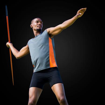 lanzamiento de jabalina: Deportista practicando el lanzamiento de jabalina en un fondo negro Foto de archivo