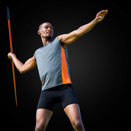 javelin: Sportsman practicing the javelin throw in a black background