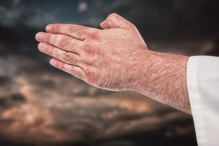 clouds making: Close-up of karate fighter making hand gesture against blue and orange sky with clouds