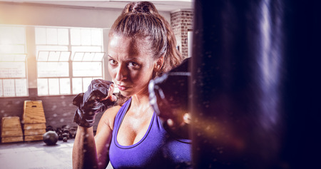 female fighter: Portrait of female fighter punching against gym