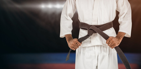 tightening: Fighter tightening karate belt against composite image of playing field indoor Stock Photo