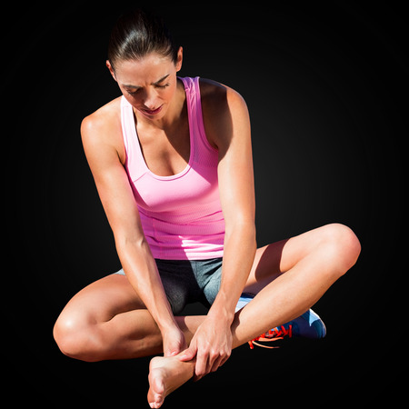 hurting: Sportswoman is hurting her foot in a black background Stock Photo