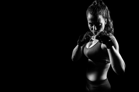 fighting stance: Portrait of woman with fighting stance against black background Stock Photo