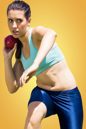 lanzamiento de bala: La deportista practicando el lanzamiento de peso contra la vi�eta amarilla Foto de archivo