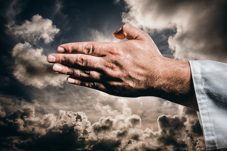 clouds making: Karate player making hand gesture on black background against dark sky with white clouds Stock Photo
