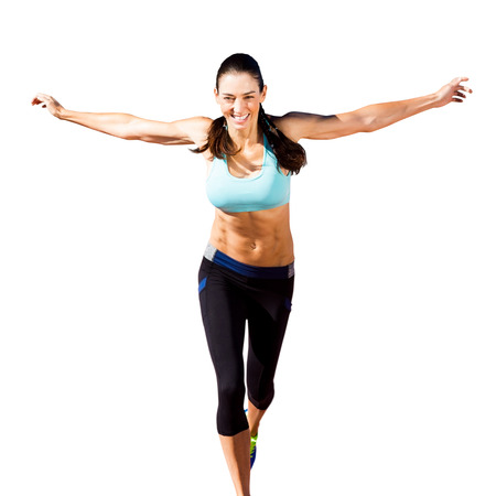 legging: Happy sportswoman is raising arms in a white background