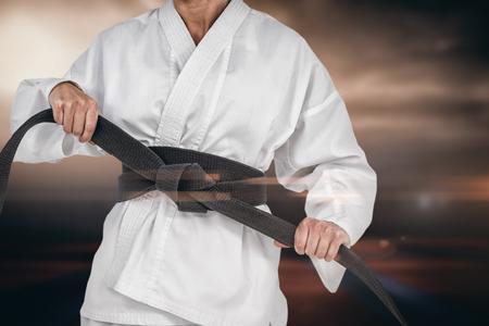 tightening: Female athlete tightening her judo belt against view of sport ground outdoor