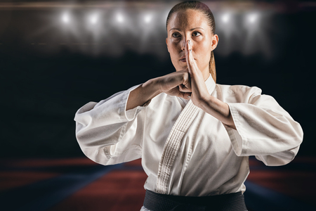 playing field: Female fighter performing hand salute against view of a playing field indoor Stock Photo