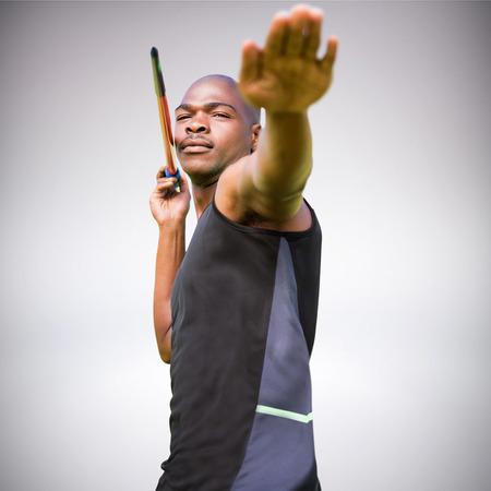 lanzamiento de jabalina: Retrato de deportista practicando un lanzamiento de jabalina contra el fondo gris