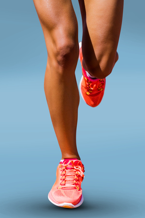 young adult woman: Close up of sportswoman legs against blue background Stock Photo