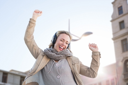 thirties: Composite image of happy woman is listening music in the street