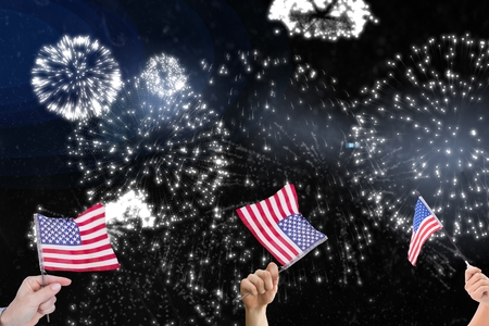 celebratory event: Composite image of hands is shaking american flags in front of firework