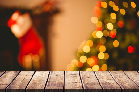 composite image: Composite image of wooden table in front of a Christmas background