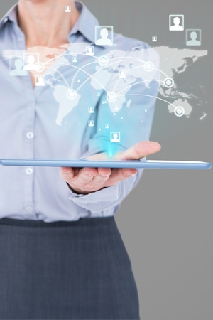 composite image: Composite image of businesswoman is holding a tablet with a hologram against a grey background
